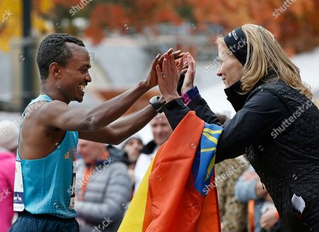 Tsegaye Kebede, Mary Wittenberg. New York Road Runners president Mary Wittenberg congratulates Tsegaye Kebede, of Ethiopia, who finished second in the men's division of the New York City Marathon, in New York