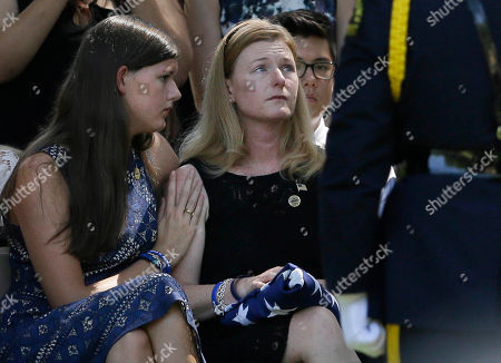 Heidi Smith, right, is comforted by her daughter Victoria Smith during graveside services for her husband Dallas police Sgt. Michael J. Smith at Restland Funeral Home and Cemetery in Dallas, . Smith was one of five police officers killed during protest in Dallas last week