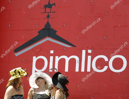 Jennifer Albright, Sarah, Evans and Jackie Boden, from left watch an early race before the 137th Preakness Stakes horse race at Pimlico Race Course, in Baltimore