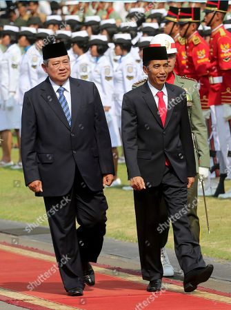 Joko Widodo, Susilo Bambang Yudhoyono. Indonesia's President Joko Widodo, right, inspects a guard of honor with his predecessor Susilo Bambang Yudhoyono at the presidential palace in Jakarta, Indonesia, . Widodo completed a journey from riverside shack to presidential palace on Monday, cheered through the streets following his inauguration by tens of thousands of ordinary Indonesians in a reminder to the opposition-controlled parliament of the strong grass-roots support that swept him to power