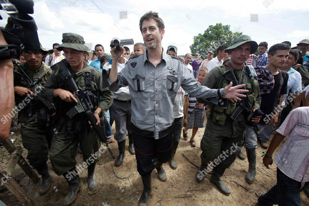 French journalist Romeo Langlois, center, is escorted by rebels of the Revolutionary Armed Forces of Colombia, FARC, upon their arrival to San Isidro, southern Colombia, . Langlois, who was taken by rebels on April 28 when they attacked troops he was accompanying on a cocaine-lab eradication mission, was handed over by the rebels to a delegation that included a French diplomat in San Isidro