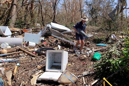 Stock Image of Pete Murray sifts through debris looking for his belongings in Tully Heads, Australia, after Cyclone Yasi brought heavy rain and howling winds gusting to 186 mph (300 kph). Yasi ripped across the coast near Cairns on Wednesday night, tearing apart dozens of homes and damaging hundreds more, cutting power to tens of thousands of people and flattening millions of dollars worth of crops
