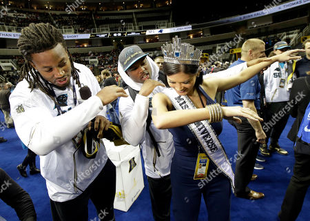 Carolina Panthers' Ryan Delaire and Bene' Benwikere dance with Miss Universe Pia Alonzo Wurtzbach during Opening Night for the NFL Super Bowl 50 football game, in San Jose, Calif