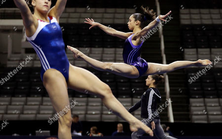 Sabrina Vega, center, warms up at the start of practice for the U.S. Olympic gymnastics trials, in San Jose, Calif