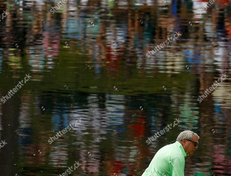 Fuzzy Zoeller putts during the par three competition at the Masters golf tournament, in Augusta, Ga