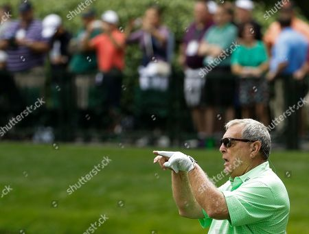 Fuzzy Zoeller has some fun on the ninth hole during the par three competition at the Masters golf tournament, in Augusta, Ga