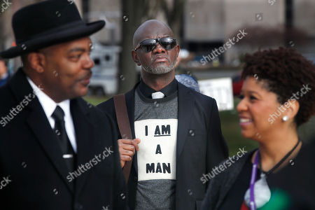 Aaron Ward, of Washington, center, attends the A.C.T. To End Racism rally, on the National Mall in Washington, on the 50th anniversary of Martin Luther King Jr.'s assassination. Milton A. Williams, left, pastor of Pennsylvania Ave. AME Zion Church in Baltimore and Ruth LaToison Ifill, with AME Zion Church, right
