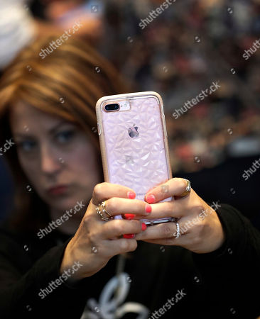 Stock Picture of A customer uses her Apple iPhone X during an Apple event at their main store, in Chicago