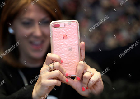 A customer uses her Apple iPhone X during an Apple event at their main store, in Chicago