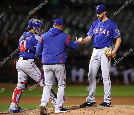 Doug Fister, Jeff Banister, Robinson Chirinos. Texas Rangers pitcher Doug Fister, right, hands the ball to manager Jeff Banister as he is removed from the baseball game against the Oakland Athletics in the fifth inning, in Oakland, Calif. At left is Rangers catcher Robinson Chirinos