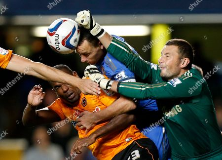 Chelsea's captain John Terry, center, heads the ball away from Ronald Zubar, left, as goalkeeper Ross Turnbull attempts to punch the ball away during the English League Cup soccer match between Chelsea and Wolverhampton Wanderers at Stamford Bridge stadium in London