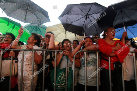 People sing and cheer during a homage to famed Mexican singer Chavela Vargas at the traditional Mariachi Garibaldi Plaza in Mexico City, . Chavela Vargas, who defied gender stereotypes to become one of the most legendary singers in Mexico, died Aug. 5 at age 93