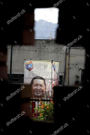 "A poster of Venezuela's President Hugo Chavez is seen through a cross-shaped window, from inside the military hospital's chapel, in Caracas, Venezuela, . A brief statement read on national television by Communications Minister Ernesto Villegas late Monday carried the sobering news about the charismatic 58-year-old leader's deteriorating health. Villegas said Chavez is suffering from ""a new, severe infection."" The state news agency identified it as respiratory"