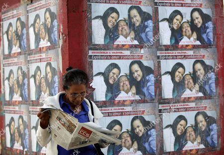"A woman reads a newspaper as she stands by a wall covered with posters showing Venezuela's President Hugo Chavez pictured with his daughters Maria Gabriela, and Rosa Virginia, outside the military hospital in Caracas, Venezuela, . A brief statement read on national television by Communications Minister Ernesto Villegas late Monday carried the sobering news about the charismatic 58-year-old leader's deteriorating health. Villegas said Chavez is suffering from ""a new, severe infection."" The state news agency identified it as respiratory"
