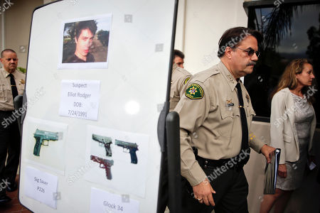 Santa Barbara County Sheriff Bill Brown, right, walks past a board showing the photos of suspected gunman Elliot Rodger and the weapons he used in Friday night's mass shooting that took place in Isla Vista, Calif., after a news conference, in Santa Barbara, Calif. Sheriff's officials say Rodger, 22, went on a rampage near the University of California, Santa Barbara, stabbing three people to death at his apartment before shooting and killing three more in a crime spree through a nearby neighborhood