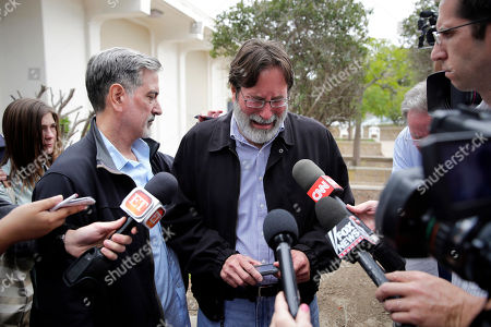 Richard Martinez, center, who says his son Christopher Martinez was killed in Friday night's mass shooting that took place in Isla Vista, Calif., is comforted by his brother, Alan, as he talks to media outside the Santa Barbara County Sheriff's Headquarters, in Santa Barbara, Calif
