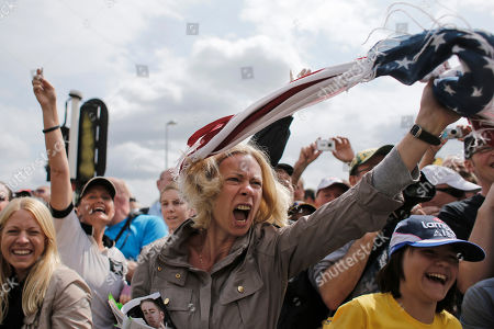 A cycling fan waves the American flag as she screams to get the attention of George Hincapie of the US prior to the start of the first stage of the Tour de France cycling race over 198 kilometers (123 miles) with start in Liege and finish in Seraing, Belgium, . Hincapie, who is riding his 17th Tour de France, came over to sign autographs