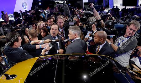 Michael Horn, center, President and CEO of Volkswagen Group of America talks to the media at the Los Angeles Auto Show, in Los Angeles
