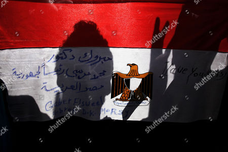 """A man's shadow is reflected on Egypt's national's flag with Arabic writing that reads, """"congratulations Dr. Mohammed Morsi president of Egypt,"""" in Tahrir square, Cairo, Egypt, . Mohammed Morsi was declared Egypt's first Islamist president on Sunday after the freest elections in the country's history, narrowly defeating Hosni Mubarak's last Prime Minister Ahmed Shafiq in a race that raised political tensions in Egypt to a fever pitch"""