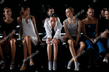 "Jing Wen, center, of Guangzhou, China, waits to rehearse with other models before the Prabal Gurung Spring 2015 collection show, during Fashion Week in New York. Jing Wen, 19, began modeling at age 17. She says that as a little girl, she loved the idea of modeling, but never dreamed that she would end up walking runways internationally. Although her mother and sister are back in China, she doesn't often suffer from homesickness. For Jing Wen, the struggle to stay emotionally balanced is far more difficult. ""You have to keep your heart strong,"" she explains. ""It's so hard to get the show, so you have to [stay] peaceful, all the time."" As for her future plans, Jing Wen sees herself as an entrepreneur. She says she plans to go back to school after modeling ""and maybe after few years I will have my coffee shop"