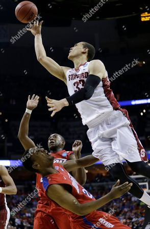 Dayton forward Dyshawn Pierre (21) falls to the court as Stanford forward Dwight Powell (33) shoots during the second half in a regional semifinal game at the NCAA college basketball tournament, in Memphis, Tenn