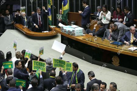 "Jose Eduardo Cardoso. Brazil's Attorney General Jose Eduardo Cardozo, top left, presents the defense of Brazil's President Dilma Rousseff in the Chamber of Deputies, as opposition lawmakers hold signs that read in Portuguese ""Goodbye dear"" and ""Impeachment now"" in Brasilia, Brazil, . The lower chamber of Brazil's Congress began the debate on whether to impeach Rousseff, a question that underscores deep polarization in Latin America's largest country and most powerful economy. The crucial vote is slated for Sunday"