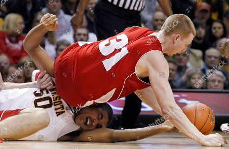Wisconsin's Mike Bruesewitz (31) scrambles for a loose ball against Minnesota's Ralph Sampson III (50) during the first half of an NCAA college basketball game, in Minneapolis