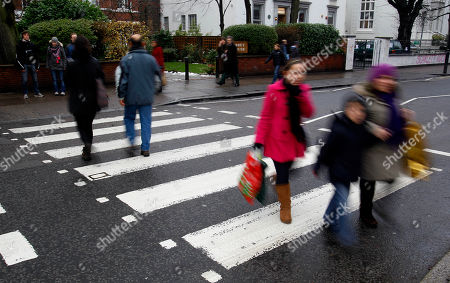 "Tourists cross over the zebra crossing in Abbey Road in London, . The world-famous zebra crossing which features on the cover of the Beatles' Abbey Road sleeve has been given ""listed"" status by the Government. The crossing - just outside the renowned Abbey Road studios, where the Beatles recorded much of their output - has been given Grade II listing by heritage minister John Penrose"