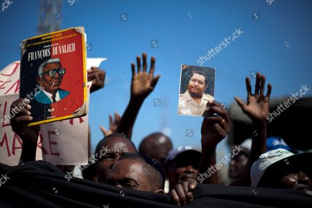 """Stock Photo of Supporters of former Haitian dictator Jean-Claude Duvalier, known as """"Baby Doc,"""" hold a picture of him, right, and of his father Francois Duvalier, known as """"Papa Doc,"""" outside a courthouse where Duvalier attends a hearing in Port-au-Prince, Haiti, . Duvalier returned to Haiti in early 2011 after spending 25 years in exile. While in exile, Duvalier remained quiet except for a September 2007 radio address in which he apologized for wrongs committed under his rule and urged supporters to rally around his fringe political party"""