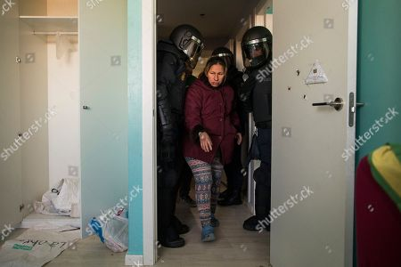Cecilia Paredes, center, prepares to leave her apartment after riot police broke down the door during the eviction of her and her family in Madrid, Spain, . Paredes, 43, and her unemployed electrician husband Wilson Ruilova, 35, both from Ecuador, have three children: Dilan, a baby born less than two months ago; Andres, 16, and Miguel, seven. They have been unable to pay their rent after she lost her job as an elderly care assistant two years ago. The government company that owned the apartment sold it last year to an investor group along with more than 1,800 other apartments built for the needy and the new owner sought the family's eviction