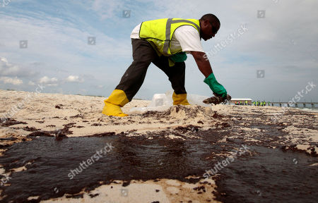 Stock Photo of Steve Gardner of Mobile scrapes oil from the sand along a 700-yard long strip of oil that washed up on the beach in Gulf Shores, Ala., . Oil from the Deepwater Horizon disaster has started washing ashore on the Alabama and Florida coast beaches