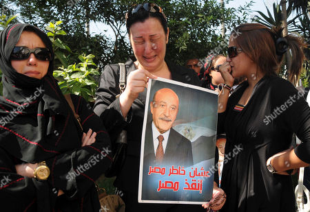 """Women mourn at the funeral for Egypt's former spy chief, Omar Suleiman, seen in the poster at center, in Cairo, Egypt, . Egypt's top military commander and mourners attended a military funeral honoring Egypt's former spy chief Omar Suleiman, who died in a U.S. hospital at the age of 76. The Arabic on Suleiman's presidential campaign poster reads, """"for the sake of Egypt, save Egypt"""