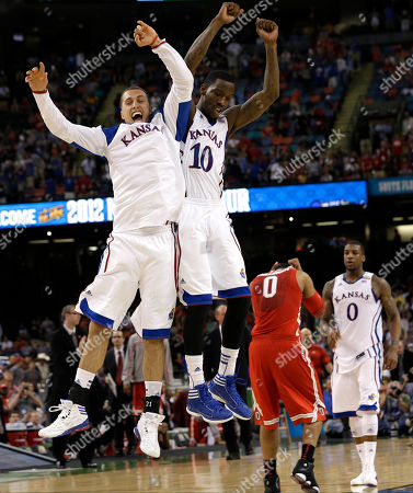 Kansas guard Tyshawn Taylor (10) celebrates with Kansas guard Christian Garrett at the end of an NCAA Final Four semifinal college basketball tournament game against Ohio State, in New Orleans. Kansas won 64-62