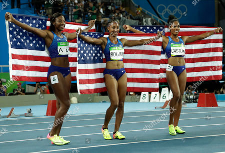 Gold medal winner Brianna Rollins, silver medal winner, Nia Ali and bronze medal winner Kristi Castlin, all from the United States, pose with their country's flag after the 100-meter hurdles final, during the athletics competitions of the 2016 Summer Olympics at the Olympic stadium in Rio de Janeiro, Brazil