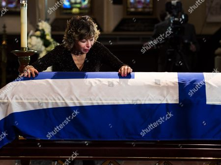 Renata Ford cries over her husband's casket at St. James Cathedral during funeral services in Toronto on . Rob Ford died of cancer last week, at the age of 46