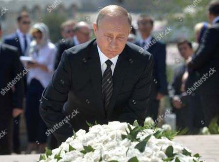 Russian President Vladimir Putin pays his last respect at a cemetery in Samarkand, Uzbekistan, . Putin arrived to express his condolences and visit a grave of Uzbekistan's President Islam Karimov in Samarkand