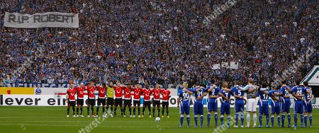 Players and fans stand for a minute of silence to commemorate late Hannover team goalkeeper Robert Enke prior to the German first division Bundesliga soccer match between FC Schalke 04 and Hannover 96 in Gelsenkirchen, Germany, . German national keeper Robert Enke of Hannover committed suicide two weeks ago