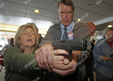 Christine Caldwell, left, receives firearms training with a 9mm Glock from personal defense instructor Jim McCarthy during concealed weapons training for 200 Utah teachers, in West Valley City, Utah. The Utah Shooting Sports Council offered six hours of training in handling concealed weapons in the latest effort to arm teachers to confront school assailants