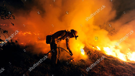 A firefighter works to put out a spot fire near Santa Barbara, Calif., . Firefighters struggled early Friday to get ahead of a raging wildfire that was moving dangerously close to heavily populated areas in this idyllic coastal city. The fire's increasing strength prompted officials to order 6,000 more people to evacuate late Thursday, Santa Barbara County Sheriff Bill Brown said. That pushed the total number of evacuated residents to at least 18,000