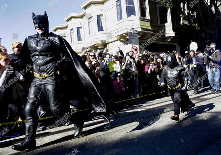 """Miles Scott, dressed as Batkid, right, runs with Batman after saving a damsel in distress in San Francisco, . San Francisco turned into Gotham City on Friday, as city officials helped fulfill Scott's wish to be """"Batkid."""" Scott, a leukemia patient from Tulelake in far Northern California, was called into service on Friday morning by San Francisco Police Chief Greg Suhr to help fight crime, The Greater Bay Area Make-A-Wish Foundation says"""