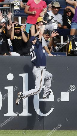Milwaukee Brewers left fielder Logan Schafer (22) leaps to catch a fly ball by Pittsburgh Pirates' Gaby Sanchez in the seventh inning of the baseball game, in Pittsburgh. The Pirates won 2-1 in 14 innings