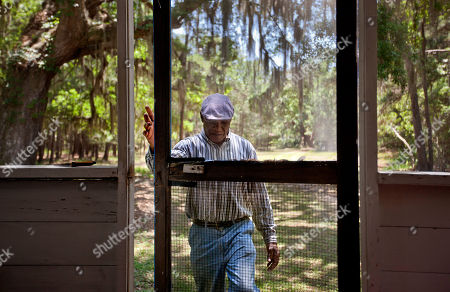 """Stephen Wilson, 68, walks onto the front porch of his home that his father built in the Hog Hammock community of Sapelo Island, Ga. on . """"Dad built this house with his labor. Every time I put the key in the door, I remember coming home as a child saying, 'Hi, papa. Hi, mama.' It has a lot of remembrance."""" Wilson is one of roughly 47 residents, most of them descendants of West African slaves known as Geechee, who remain on the coastal Georgia island where their ancestors were brought to work a plantation in the early 1800s. Isolated over time to the Southeast's barrier islands, the Geechee of Georgia and Florida, otherwise known as Gullah in the Carolinas, have retained their African traditions more than other African American communities in the U.S. Once freed, the slaves were able to acquire land and created settlements on the island, of which only the tiny 464-acre Hog Hammock community still exists. Eight children catch a ferry every morning to attend school on the mainland since the last school operating on the island closed in 1978. Residents say a sudden tax hike, lack of jobs, and development is endangering one of the last remaining Geechee communities from Florida to North Carolina"""