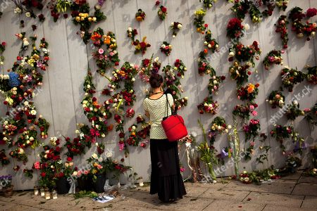 A woman is seen in front of wall decorated with flowers in memory of the victims of Friday's bomb attack and shooting rampage in Oslo, Norway, . The defense lawyer for Anders Behring Breivik said Tuesday his client's case suggests he is insane, adding that someone has to take the job of defending him but that he will not take instructions from his client. Geir Lippestad told reporters that the suspect in the bombing on the capital and the brutal attack on a youth camp that killed at least 76 people is not aware of the death toll or of the public's response to the massacre that has rocked the country