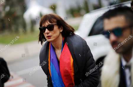 """Vladimir Luxuria, a former Communist lawmaker in the Italian parliament and prominent crusader for transgender rights, wears a rainbow scarf, while walking through central Sochi, Russia, home of the 2014 Winter Olympics. Luxuria said she was detained by police at the Olympics after being stopped while carrying a rainbow flag that read in Russian: """"Gay is OK."""" Police on Monday denied this happened"""