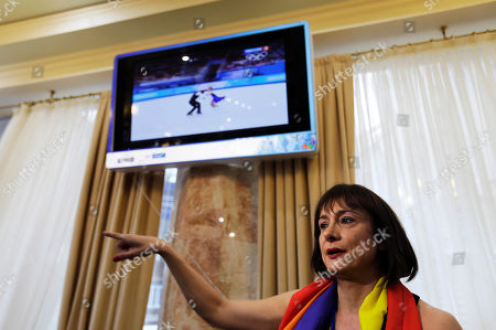 """Vladimir Luxuria, a former Communist lawmaker in the Italian parliament and prominent crusader for transgender rights, recalls how she was detained by police as she sits for an interview, in central Sochi, Russia, home of the 2014 Winter Olympics. Luxuria said she was detained by police at the Olympics after being stopped while carrying a rainbow flag that read in Russian: """"Gay is OK."""" Police on Monday denied this happened"""