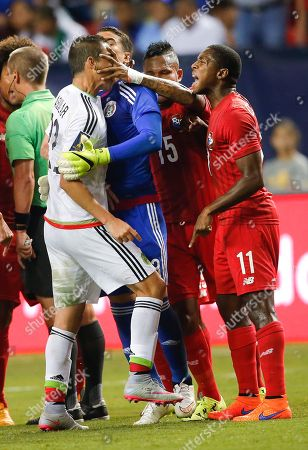 Paul Aguilar, Erick Davis, Armando Cooper, Guillermo Ochoa. Mexico's Paul Aguilar (22) gets a hand to his face from Panama's Erick Davis (15) as he argues with Armando Cooper (11), and is restrained by goalkeeper Guillermo Ochoa during the first half of a CONCACAF Gold Cup soccer semifinal, in Atlanta