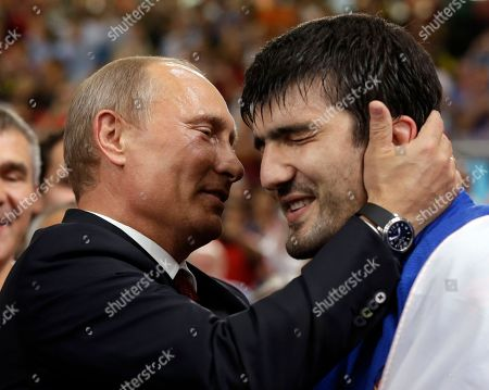 Russian President Vladimir Putin congratulates Tagir Khaibulaev of Russia after he beat Tuvshinbayar Naidan of Mongolia to win the gold medal during the men's 100-kg judo competition at the 2012 Summer Olympics, in London