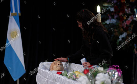 A woman caresses the head of Argentine writer Ernesto Sabato during his wake in Buenos Aires, Argentina, . Sabato, who led the government's probe of crimes committed by Argentina's dictatorship, died at 99 of complications of bronchitis, his friend and collaborator Elvira Gonzalez Fraga told local media