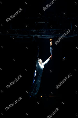 Retired Canadian sprinter Donovan Bailey is lowered to the stage with the Pan Am torch during the opening ceremony of the 2015 Pan Am Games In Toronto