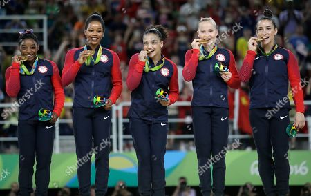 U.S. gymnasts, left to right, Simone Biles, Gabrielle Douglas, Lauren Hernandez, Madison Kocian and Aly Raisman hold their gold medals during the medal ceremony for the artistic gymnastics women's team at the 2016 Summer Olympics in Rio de Janeiro, Brazil